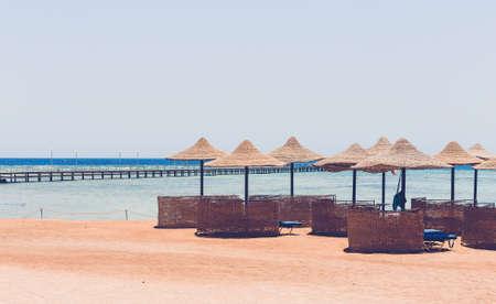 Parasols et fond de ciel bleu dans egypte plage paradisiaque. vacances d'été de concept de vacances. Personne. Tonalité de couleur de rétro