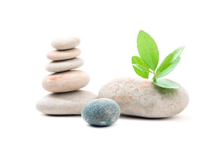 Pile of balancing pebble stones and green leaf, like ZEN stone, isolated on white background, spa welness tranquil scene concept with reflection