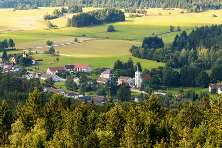 Aerial view from lookout U Jakuba to czech landscape known as Czech Canada. Touristic place. View to forest, field, meadows and small village with rural church in sunny day with blue sky Stock Photo