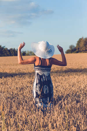 lifted hands: Middle aged beauty woman in a summer dress with summer hat relaxing in countryside with lifted hands, summer concept with evening sun