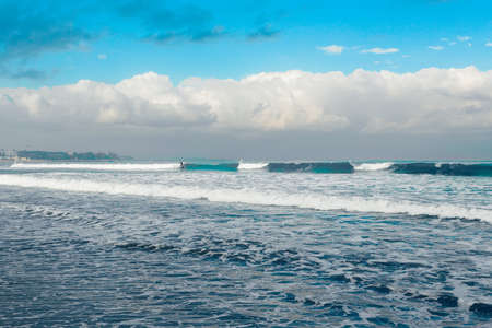 kuta: morning on Kuta beach in Bali Indonesia with unknown surfers, blue tone