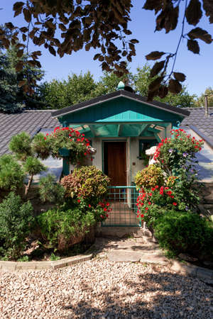 Dog baby garden house with flowers on breeding dog station. Summer garden design with flowers in bloom. Morning blue sky