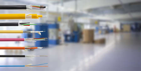 Collection of fiber optical cables on blurry production room background. Loose tubes with optical fibres and central strenght member, waterblocking glass yarn and ripcord, multimode or single mode