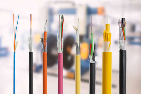 strenght: Collection of fiber optical cables on blurry production room background. Loose tubes with optical fibres and central strenght member, waterblocking glass yarn and ripcord, multimode or single mode