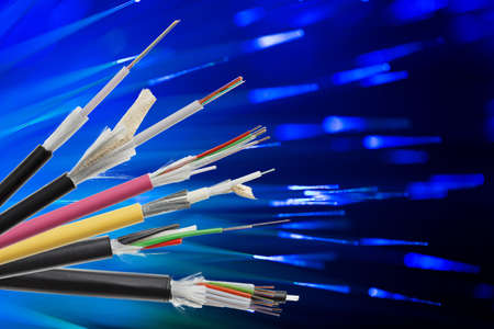 strenght: Collection of fiber optical cables on blurry technology background. Loose tubes with optical fibres and central strenght member, waterblocking glass yarn and ripcord, multimode or single mode Stock Photo