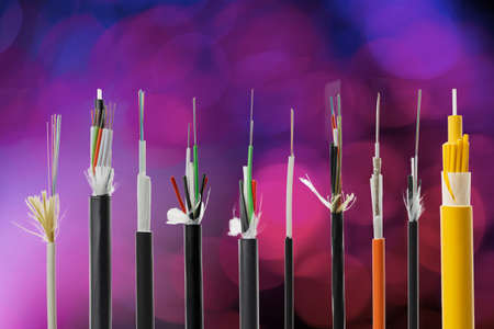 Collection of fiber optical cables on blurry bokeh background. Loose tubes with optical fibres and central strenght member, waterblocking glass yarn and ripcord, multimode or single mode