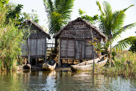 Madagascar traditional rural landscape with fisherman hut in Tamatave province near Maroantsetra city with traditional boat. Countriside wilderness virgin natural scene in North eastern Madagascar