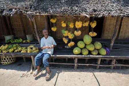 destitution: MADAGASCAR OCTOBER 17.2016 Malagasy old man selling fruit on the market near road, Toamasina Province, October 17. 2016, Madagascar, Africa