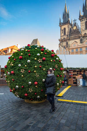 Beautiful middle age woman in Prague Old Town square, with tree decorated as christmas ball