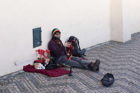 most creative: PRAGUE, CZECH REPUBLIC - DECEMBER 3, 2016: Old musician with vintage musical instrument behind Prague castle. December 3, 2016 Prague, Czech Republic.