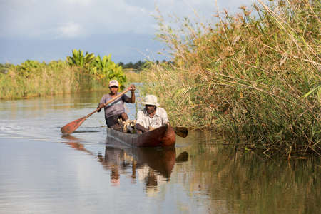 penury: MADAGASCAR OCTOBER 18.2016 Malagasy countryside people from village transport freight by Traditional handmade dugout wooden boat. Everyday life on the river. Maroantsetra October 18. 2016, Madagascar. Editorial
