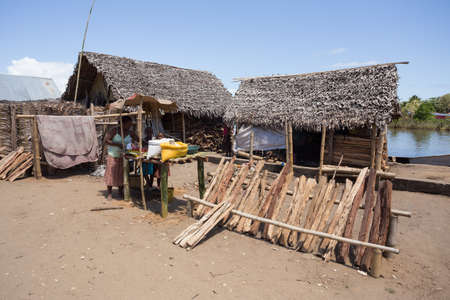 beggary: MADAGASCAR OCTOBER 18.2016 Malagasy peoples on Maroantsetra main street with firewood market and traditional huts. Wood is used for cooking on fire. Peoples everyday life in Madagascar. October 18. 2016, Madagascar, Toamasina Province Editorial