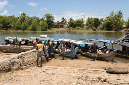destitution: MADAGASCAR OCTOBER 18.2016 Malagasy peoples waiting on port for taxi boat at embankment of river Antainambalana in city Maroantsetra, Toamasina Province. Peoples everyday life in Madagascar. October 18. 2016, Madagascar Editorial