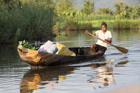 MADAGASCAR OCTOBER 18.2016 Malagasy countryside people from village transport freight by Traditional handmade dugout wooden boat. Everyday life on the river. Maroantsetra October 18. 2016, Madagascar. Editorial