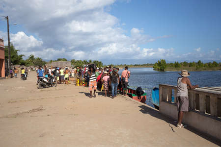 penury: MADAGASCAR OCTOBER 18.2016 Malagasy peoples waiting on port for taxi boat at embankment of river Antainambalana in city Maroantsetra, Toamasina Province. Peoples everyday life in Madagascar. October 18. 2016, Madagascar Editorial