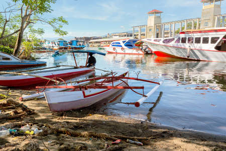 poor houses with sheet tin by the river with boats on the river,Kota Manado, North Sulawesi, Indonesia