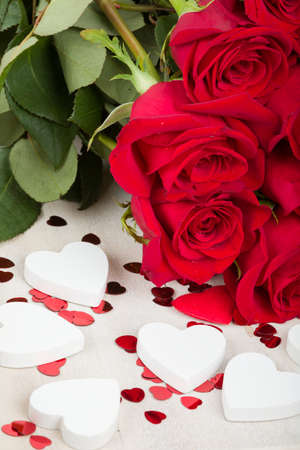 Valentine gift with bouquet of fresh red roses and small red hearts. Love concept.