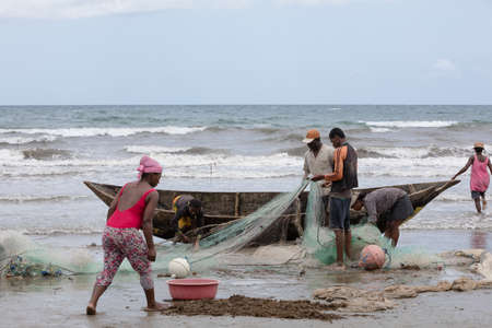 penury: MAROANTSETRA, MADAGASCAR OCTOBER 19.2016 Native fishermen fishing on sea, using traditional technique pulling net from boat. Life of indigenous peoples in countryside. October 19. 2016, Madagascar