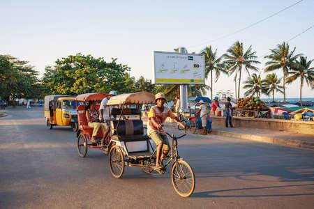 penury: TOAMASINA, MADAGASCAR - OCTOBER 17, 2016: Traditional rickshaw bicycle with malagasy peoples in Madagascar second largest city Toamasina. Ordinary street life in Toamasina, Madagascar October 17. 2016 Editorial