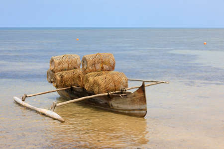 Typical malagasy bamboo woven crustacean fishing trap and catamaran on beach in Nosy Be. Madagascar rural scene.