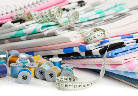tailored: cotton fabric material, tailor measurement tape with spools of thread cotton