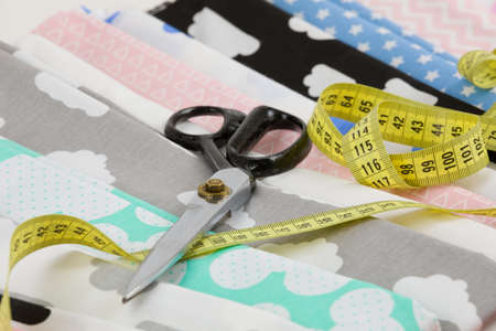 tailored: cotton fabric material and tailor measurement tape with scissors