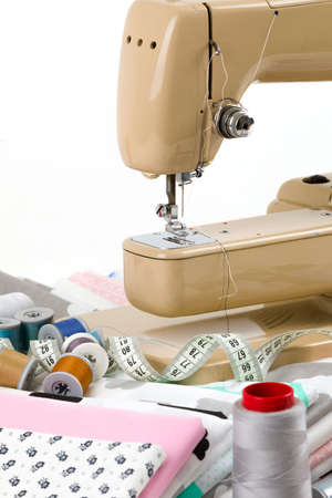 Sewing machine, cotton cotton fabric and tailor measurement tape with spools of thread cotton isolated on white