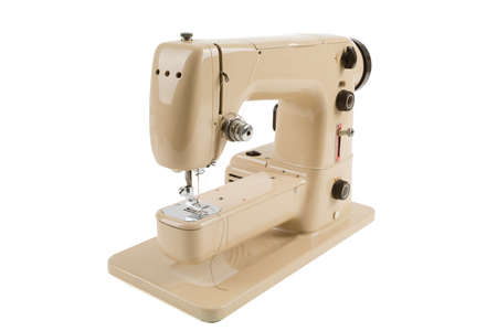 Old vintage beige sewing machine isolated on white background