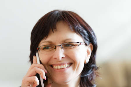 median: beautiful middle-aged smiling housewife woman without makeup call by phone