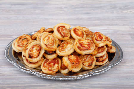 homemade bacon snail like Hawaiian pizza rolls with serving plate on vintage wooden background Stock Photo