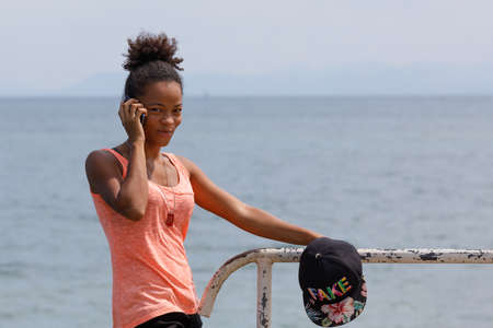 NOSY BE ,MADAGASCAR - NOVEMBER 3.2016 Malagasy young beauty woman take phone call in Nosy Be port. Nosy be, Madagascar, November 3. 2016