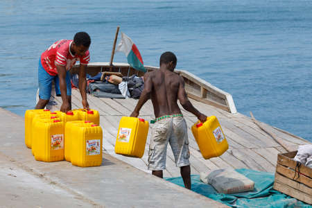 NOSY BE ,MADAGASCAR - NOVEMBER 3.2016 Malagasy men transport cargo from ship in port of Nosy Be, Madagascars largest and busiest tourist resort. Nosy be, Madagascar, November 3. 2016