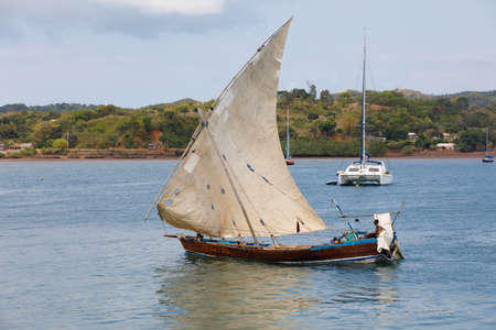 NOSY BE ,MADAGASCAR - NOVEMBER 3.2016 Malagasy man on sea in traditional handmade dugout wooden sailing boat. Everyday life on Nosy be island. Nosy be, Madagascar, November 3. 2016 Editorial