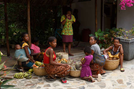 NOSY BE ,MADAGASCAR - NOVEMBER 3.2016 Malagasy women preparing baskets of fruit for street market sale. Nosy be, Madagascar, November 3. 2016 Editorial