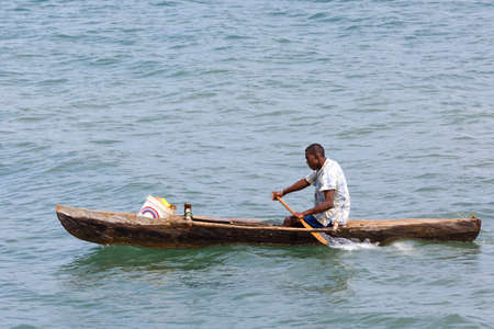 NOSY BE ,MADAGASCAR - NOVEMBER 3.2016 Malagasy man on sea in traditional handmade dugout wooden boat. Everyday life on Nosy be island. Nosy be, Madagascar, November 3. 2016 Editorial