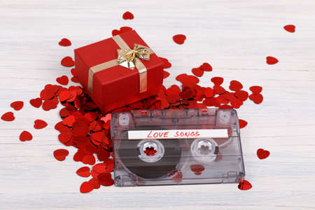 Audio cassette tape with present box, label text love songs on wooden background. Stock Photo