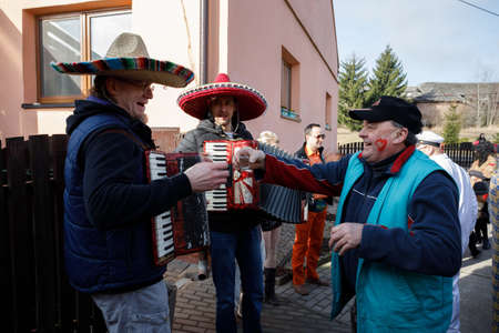 PUKLICE, CZECH REPUBLIC - MARCH 4, 2017: People attend the Masopust Carnival, a traditional ceremonial door-to-door procession in small village. March 4, 2017 in Puklice, Czech Republic