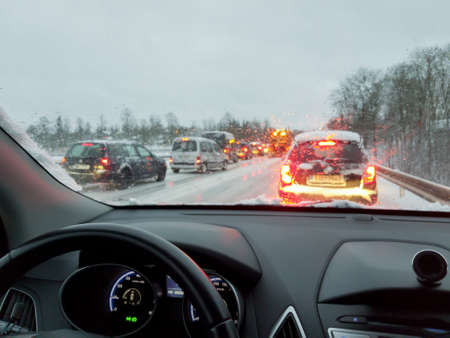 snowstorm, poor car driving on slick roads and lots of traffic, snow plow doing snow removal during blizzard Stok Fotoğraf