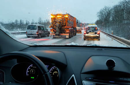 snowstorm, poor car driving on slick roads and lots of traffic, snow plow doing snow removal during blizzard Stock Photo