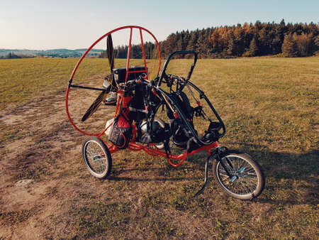 Powered paragliding vehicle on field with green grass, prepared for the flying
