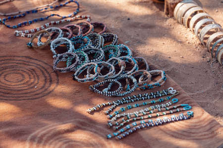 traditional souvenirs from himba peoples for tourists, exposed on sandy earth. This is Africa. Himba are indigenous peoples living in northern Namibia, in the Kunene Region (formerly Kaokoland) Stock Photo