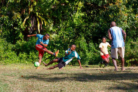 Maroantsetra, Madagascar - November 23 2016: Malagasy mans and boys, some with bare feet play soccer behind his village, near Masoala rainforest in Madagascar.