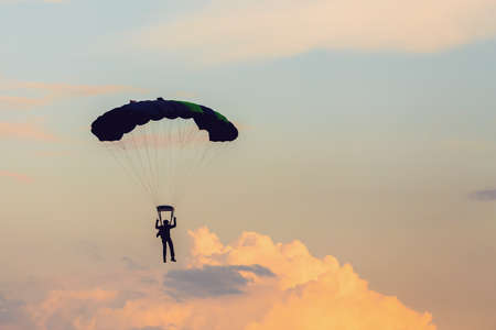Parachutist falling from the sky in evening sunset dramatic sky. Recreational sport, Paratrooper silhouette on colored sky. Stock Photo