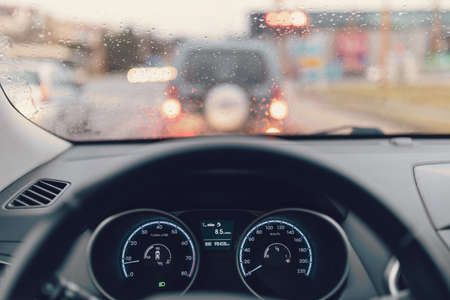 traffic jam, driving car in city, close up of steering wheel in rainy day