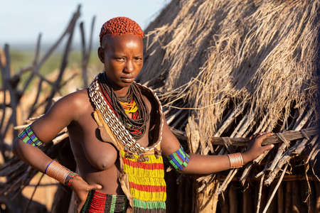 Turmi, Omo River Valley, Ethiopia - May 10, 2019: Portrait of a Hamar woman in village. The Hamer are a primitive tribe and the women have many decorations. South Ethiopia Africa Redakční
