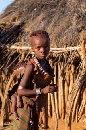 Turmi, Omo River Valley, Äthiopien - 10. Mai 2019: Porträt eines Hamar-Kinder mit Baby auf dem Rücken im Dorf. Die Hamer sind ein primitiver Stamm und die Frauen haben viele Dekorationen. Südäthiopien Afrika