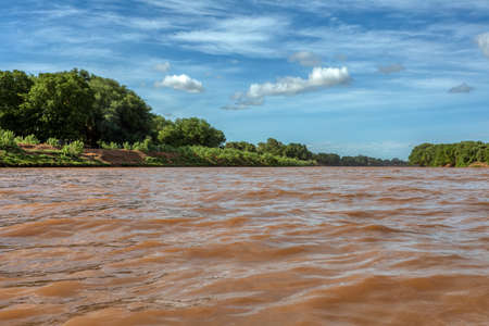 Omo River valley, home of wild Ethiopian peoples, African wilderness. Landscape of Omo River view from small wooden boat. Ethiopia, Africa Stok Fotoğraf