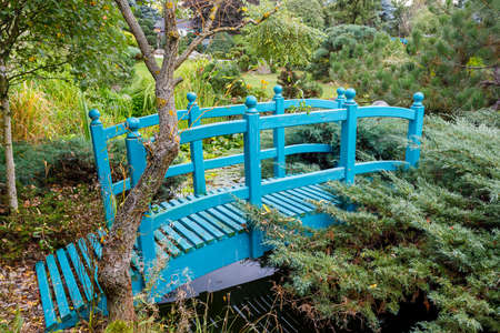 small turquoise garden bridge, footbridge over a garden Lake. garden architecture concept.