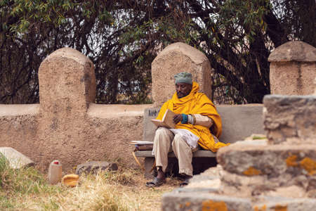 AXUM, ETHIOPIA, APRIL 27.2019, Resting orthodox priest in front of old cathedral of Our Lady of Zion on April 27, 2019 in Aksum, Ethiopia, Africa 新聞圖片
