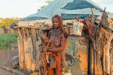 NAMIBIA, OMUSATI-REGION, 6. MAI: Himba-Leute im Dorf bei ihren täglichen Aktivitäten, Frau, die ihr Kind stillt. Himba sind indigene namibische Ethnien, im Norden Namibias, 6. Mai 2018, Namibia